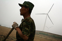 A farmer takes a break from working his land which is next to a wind turbine farm in Hebei Province, China.