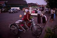 A novice monk waits on a trishaw at the docks in Rangoon (Yangon)