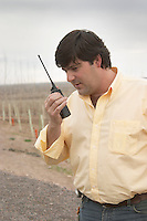 Leonardo Puppato winemaker in front of the vineyard. busy talking in a walkie-talkie Bodega Familia Schroeder Winery, also called Saurus, Neuquen, Patagonia, Argentina, South America