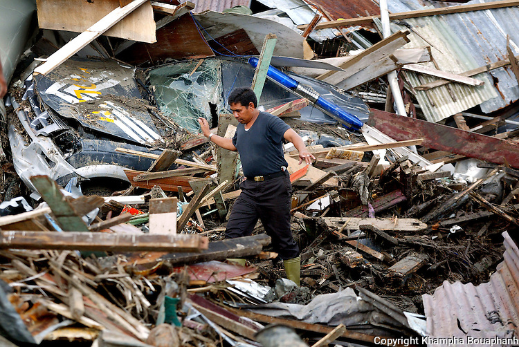 An Indonesian police officer walks through the debris at a destroyed police station in Banda Aceh on January 17, 2005.  Officials estimated over 110,000 were killed Indonesia from the Asian tsunami.  (photo by Khampha Bouaphanh)