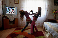 Twin sisters Florina and Roxina Stan dance in their room at their family's house. Buzescu is known for it's ultra-wealthy Roma and their bizarre mansions that line the main street. The Roma of Buzescu are part of the Kalderash clan and are known for being coppersmiths and dealing with metal scraps. After the fall of the communist regime in the late 80's, they stripped old factories of their metals and some made a small fortune re-selling them. They are also known for making cazane, copper stills that produce alcohol such as palinka, a plum brandy.