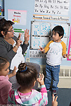 Education Preschool 3-4 year olds female teacher with small group doing counting numbers activity