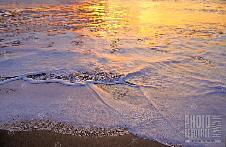 Beautiful close-up of foam and water on the shoreline of Hanakanaia Beach on Kahoolawe, reflecting the golden sunset.