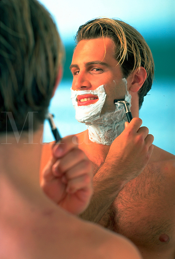 handsome young white blonde man shaving in front of mirror. Mike. United States photo studio.