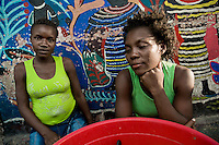 Haitian girls sell fruits in the La Saline market, Port-au-Prince, Haiti, 23 July 2008. Every day thousands of women from all over the city of Port-au-Prince try to resell supplies and food from questionable sources in the La Saline market. The informal sector significantly predominate within the poor Haitian economics and the regular shops virtually do not exist. La Saline is the largest street market area in Port-au-Prince.