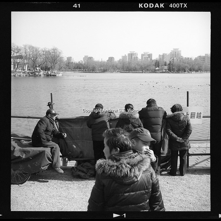 Chinese visitors look at a pond at a temple fair during the Chinese New Year in Beijing, China, February, 2014. (Mamiya 6, 75mm, Kodak TRI-X film)