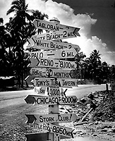 It doesn't seem to matter where the war has carried the GI.  He retains a keen sense of humor and an equally sharp yearning for home.  Signpost at a crossroads in Tacloban on Leyte reflects Joe's love of a gag and names and places he misses.  Ca.  1944-45.  (Coast Guard)<br /> Exact Date Shot Unknown<br /> NARA FILE #:  026-G-4650<br /> WAR & CONFLICT BOOK #:  1213