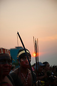 An indigenous participant hold his bow and arrow during the fire ceremony at sunset at the International Indigenous Games in Brazil. 22nd October 2015