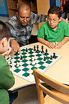 Afterschool chess program for elementary students graduates of Headstart program male teacher working with children