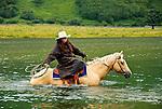 Rochelle riding across the Pasagshak River, Kodiak Island, Alaska