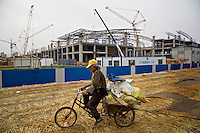 A farmer scavenges on a bicycle around a new stadium  - erected over former farmland - for building materials in Linyi. The local government is razing down farmland on the outskirts of the city and turning farmland into an urban development zone. The Chinese government plans to move 250 million rural residents into urban areas over the coming dozen years though it is unclear whether people want to move and where the money for this project will come from. Further urbanisation is meant to drive up consumption to counterbalance an export orientated economy and end subsistence farming but the drive to get people off the land is causing tens of thousands of protests each year. /Felix Features