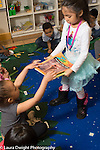 Education Preschool 3-4 year olds classroom job girl collecting picture books before circle time begins