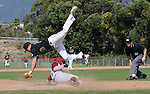 Third baseman is upended by player sliding into third.