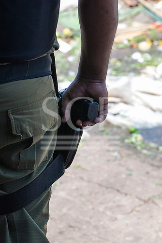 Belem, Para State, Brazil. Armed Police hand gun during a demonstration against the construction of the Belo Monte hydroelectric dam, 20th August 2011.