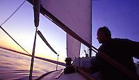 Man sailing at sunset in smooth seas
