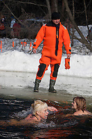 Moscow, Russia, 08/03/2010..A lifeguard watches as women of the Moscow Ice Swimming Club celebrate International Women's Day with a swim and party at a frozen lake in northern Moscow. The club always hold their end of season party on Women's Day.