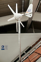 Small wind turbine which at the Able Skills Training Centre, Dartford, Kent.  Wind turbines turn the spinning energy of the blades into electricity.
