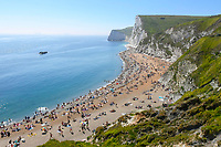 BNPS.co.uk (01202 558833)<br /> Pic: Graham Hunt/BNPS<br /> <br /> What a difference a year makes..<br /> <br /> The windswept beach at Durdle Door in Dorset is virtually deserted today, exactly a year after glorious weather saw thousands flock to the iconic landmark. <br /> <br /> A few stragglers, wrapped up in hats and coats, braved the wind and rain to walk along the beach that became a magnet for sunseekers during last year's pandemic.<br /> <br /> Whilst last year saw temperatures into the mid-20s - way above the average for May - today the thermometer struggled to reach 10C.<br /> <br /> <br /> (This picture was taken on 20/5/20)