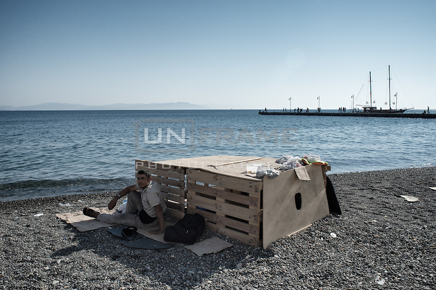 Syrian and his makeshift beach cabin made of transportation pallets. The roof doubles as storage. Wooden sailboat on pier in the background.  Kos, Greece. Sept. 6, 2015