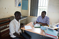 N. Uganda, Gulu District. Peter C. Alderman Foundation project. Joshua Tugumisirize, psychiatrist & Freddy Odong, nurse, assessing and counseling Christine Alum. Christine lost her arm during the war and struggles with depression. She has a son who helps her.