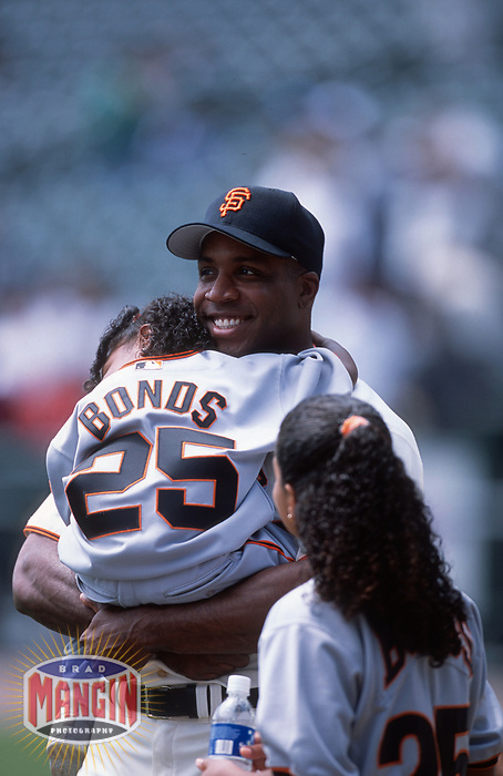 SAN FRANCISCO, CA:  Barry Bonds of the San Francisco Giants smiles on the field with his daughters Shikari Bonds and Aisha Bonds before a game at Pacific Bell Park in San Francisco, California in 2001. (Photo by Brad Mangin)
