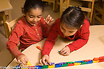 Preschool  horizontal 4-5 year olds two girls playing together with construction toy road and small plastic dinosaurs