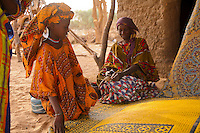 In Oursi village in Burkina Faso granddaughter admires the colorful straw<br /> carpets made by her grandmother