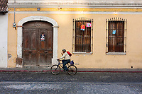 Antigua, Guatemala.  Street Scene, Man Riding Bicycle.