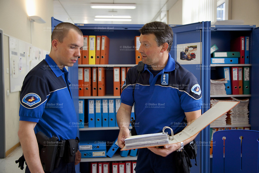 Switzerland. Geneva. A police officer (R) with the rank of brigadier explains the diverse binders to a young policeman (L) who is still finishing his police academy training program by making his last practical internship at the Paquis police station. A police station or station house is a building which serves police officers and contains offices, temporary holding cells and interview/interrogation rooms. 14.05.12 © 2012 Didier Ruef