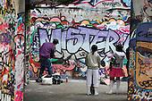 Young man paints graffiti on a wall at the South Bank, London.