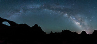 A panorama of the Milky Way arcing over Sunset Arch in Arches National Park, Utah.