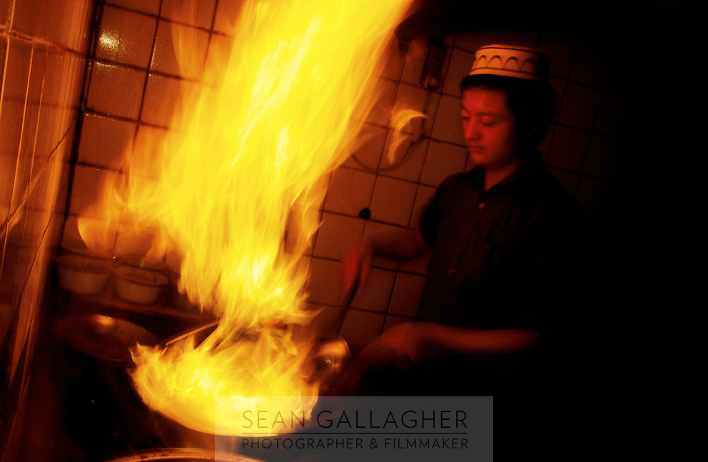 CHINA. Beijing. A young Muslim man cooking in his family's restaurant. 2005