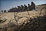 © Remi OCHLIK/IP3 -  Benghazi March 24, 2011 - Rebel fighters pray on the frontline..Opposition fighters hold their position at 9 kilometers from Adjabyia still occupied by the loyalist forces