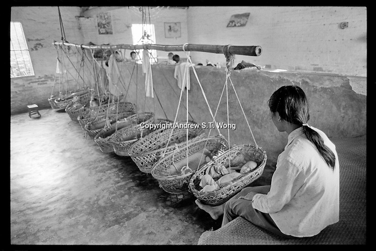 A Chinese nurserymaid looks after toddlers sleeping in hanging baskets at a nursery set up to take care of children of farmers at a village in Guangdong province, China, 1988.