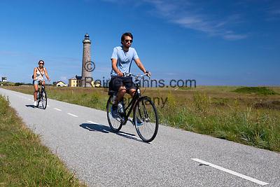 Denmark, Jutland, Skagen: Cyclists on Cycle path along Fyrvej with Skagen Fyr (lighthouse) behind   Daenemark, Juetland, Skagen: auf dem Fyrvej Radweg am Leuchtturm Skagen Fyr entlang