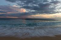Surfers enjoy the waves at sunset at Yokohama Bay on the West Coast of O'ahu.