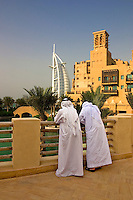 Dubai, United Arab Emirates. Madinat Jumeirah. Burj al Arab Hotel and Mina A'Salam Hotel. Two Arab men enjoying the view from the terrace of the souk/bazaar..