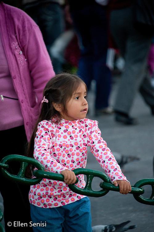 Arequipa, Peru. Young child (Peruvian) holds onto large chain in public park. No MR. ID: AL-peru.