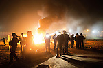 "© Joel Goodman - 07973 332324 . 23/10/2016 . Calais , France . Riot police in front of a fire set by residents , at the Calais migrant camp known as "" The Jungle "" , in Northern France , on the evening before the start of the eviction and destruction of the camp . Photo credit : Joel Goodman"