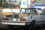 OLD DAMAGED CAR AT GAS STATION