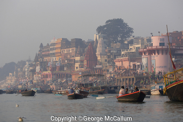 Rowing boats with tourists on Ganges river, outside of Dashashwamedh Ghat, Varanasi, India