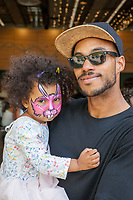 Man holding his face painted daughter, NWFolklife Festival, Seattle, WA, USA.