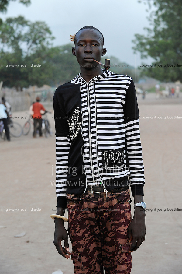 SOUTH SUDAN  Bahr al Ghazal region , Lakes State, town Rumbek , portrait of young Dinka man with tobacco pipe and Prada jacket