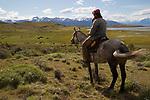 Argentina,  Patagonia, El Calafate:  Gaucho on horseback looking over ranch at Estancia Alta Vista to The Andes | Argentinien, Patagonien, El Calafate: Gaucho auf der Estancia Alta Vista, im Hintergrund die Anden