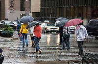 Downtown office workers cross Congress Ave. at 6th Street holding umbrellas during a rainy day in Austin, Texas.