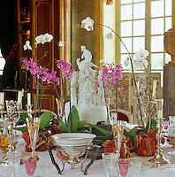 The dining table has been laid around a marble centrepiece, potted orchids and silver candlesticks and set with a colllection of antique glasses