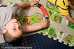 Education Preschool 4-5 year olds.Education preschool 4-5 year olds portrait of boy looking up from playing with truck on floor mat horizontal
