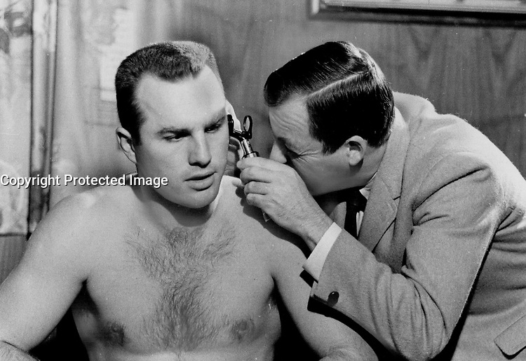 Anything wrong; doc? Right winger Ron Ellis appears a trifle concerned as Dr. Bob MacMillan checks ear during medical given each player prior to start of training camp. Maple Leafs took to ice for first skate of season at Peterborough yesterday and doctors reported all 25 in surprisingly good condition.<br /> <br /> Photo : Boris Spremo - Toronto Star archives - AQP