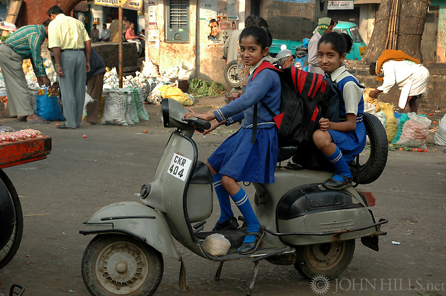 Two young Indian girls on a scooter in Bangalore waiting for their father who is buying vegetables at the Russell market.Girls are wearing school uniforms and have backpacks. It is common in India for a whole family to ride on a single motorcycle.