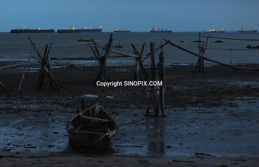 Large ships moored off the coastline close to Sunghai Rengit, southern Malaysia. There are hundreds of container ships and oil tankers moored in a 30 km stretch that are disrupting the livelihoods of many fisherman in the area.